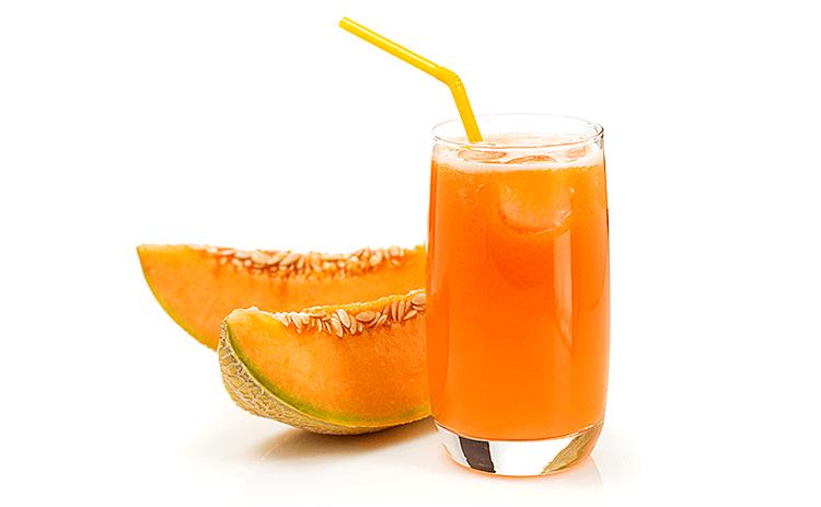 Bicchiere con succo di melone e fette di melone