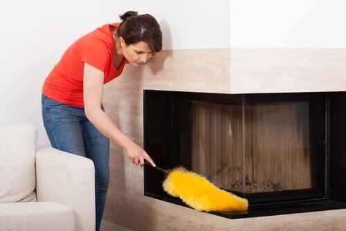 Donna che pulisce la polvere dai mobili