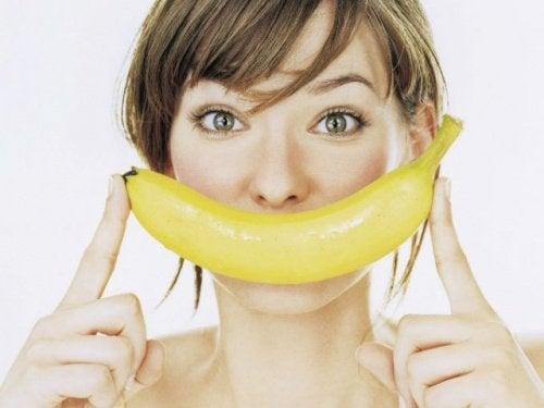 Donna con banana vicino al viso