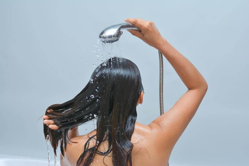Donna sotto alla doccia che si lava capelli