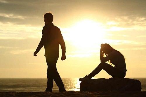 donna seduta su scoglio al mare e uomo che si allontana