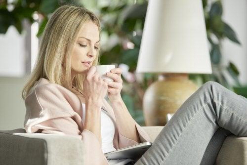 Donna seduta beve infuso contro il mal di testa