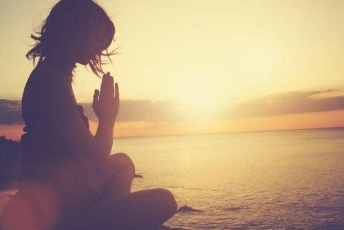 Donna medita vicino al mare