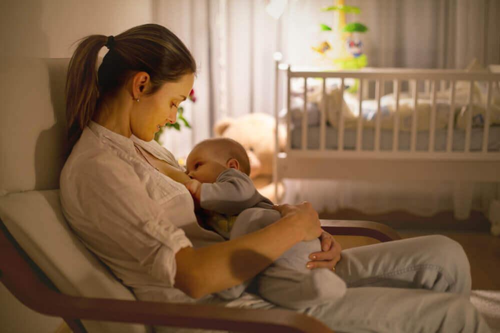Madre che allatta il suo bambino nella cameretta