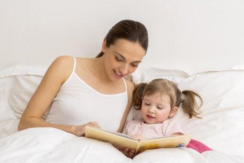 Mamma che legge una favola alla figlia a letto