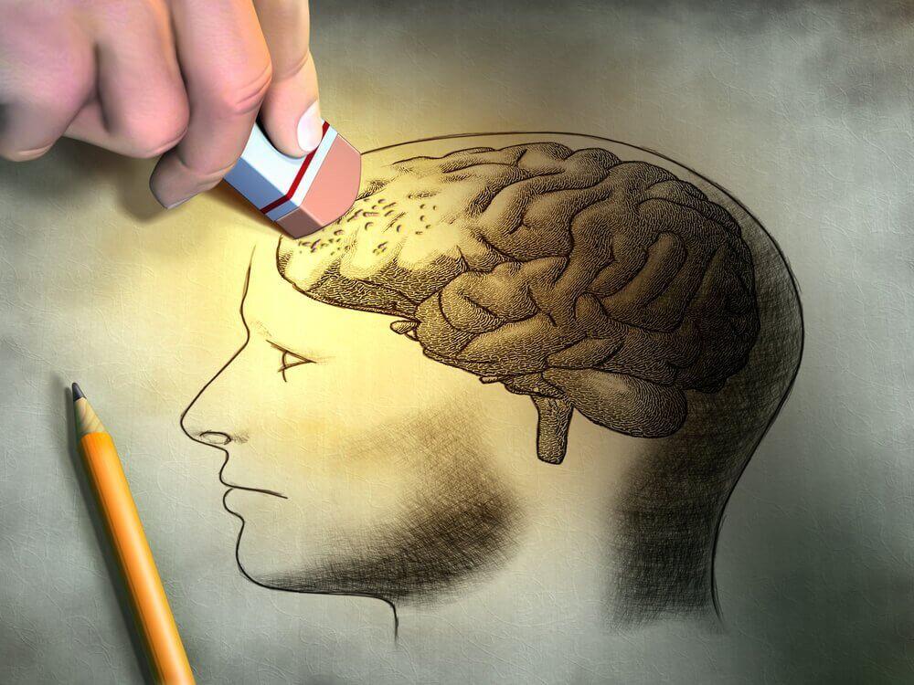 Mano che cancella cervello disegnato su foglio