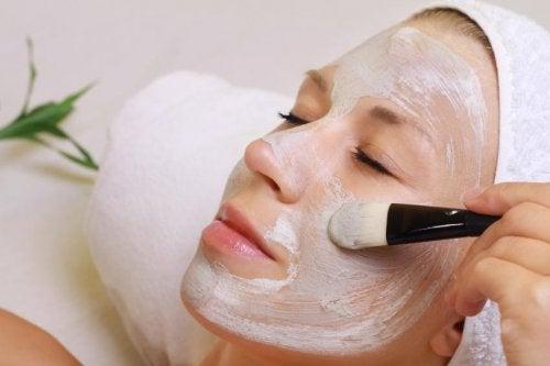 Donna applica maschera sul viso con un pennello