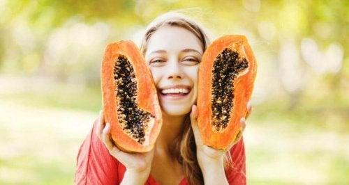 Ragazza tiene in mano papaya.