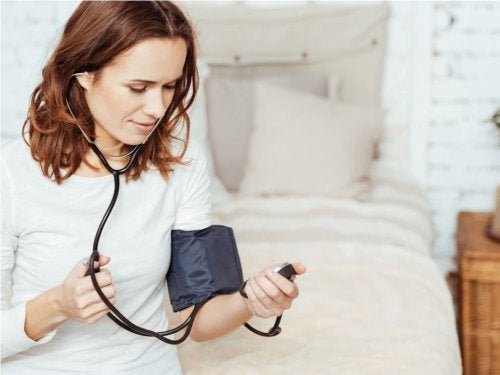 Donna che misura pressione arteriosa