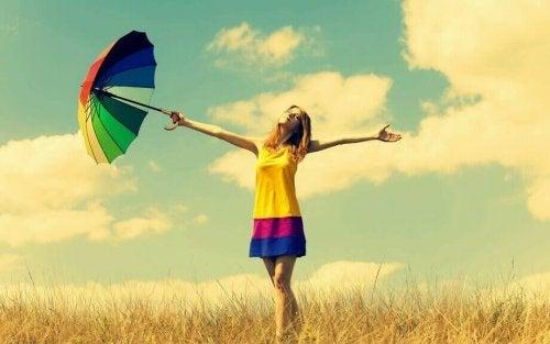 Ragazza in campagna con vestito e ombrello colorati
