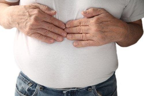 Uomo con mani sullo stomaco