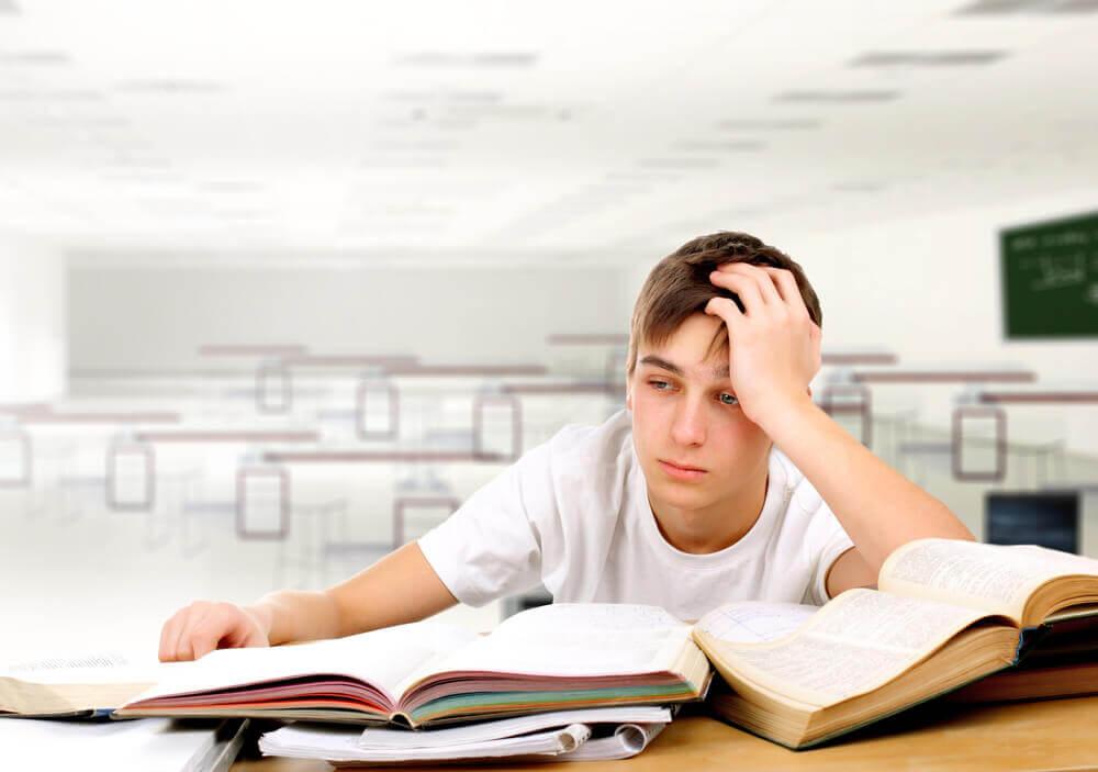 Adolescente esausto davanti ai libri