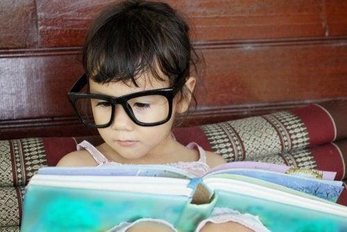 Bambina piccola con occhiali legge a letto