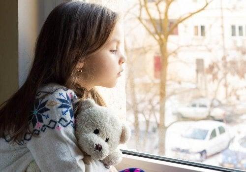 Bambina triste che guarda dalla finestra
