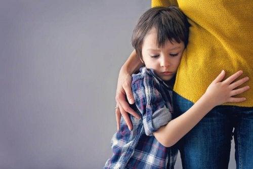 Bambino abbracciato alle gambe della mamma
