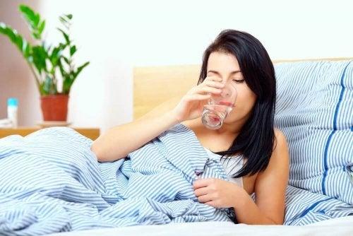 Donna beve acqua a letto