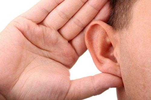 Uomo con mano dietro l'orecchio