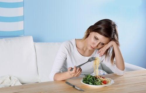Donna depressa che guarda piatto con cibo