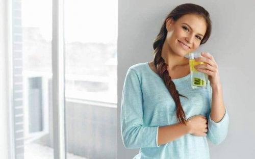 Donna con un bicchiere di acqua e limone