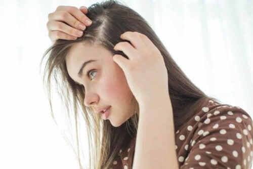 Ragazza che osserva i propri capelli.