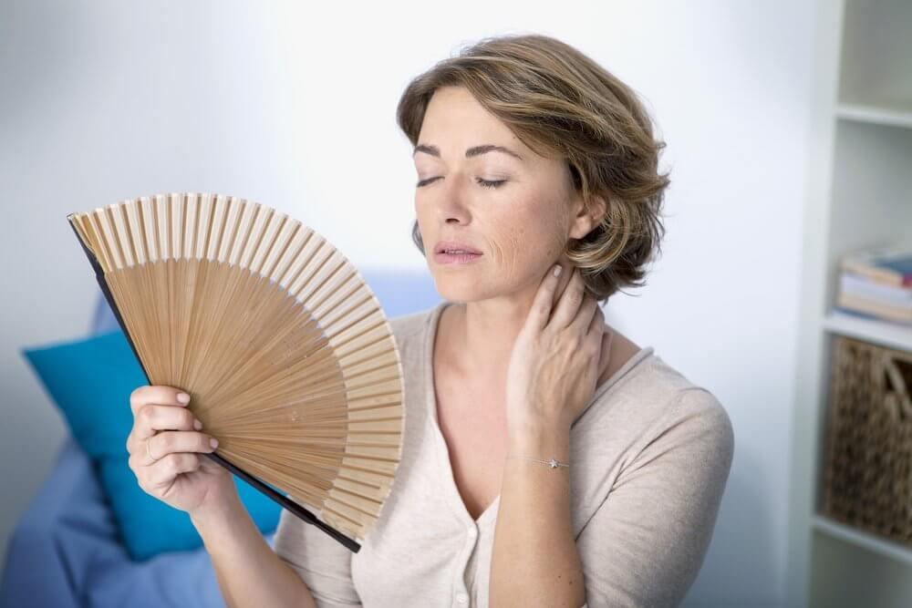 Donna in menopausa che si fa vento con ventaglio