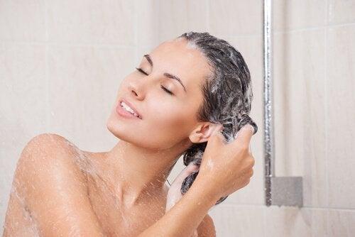 Donna si lava i capelli sotto la doccia