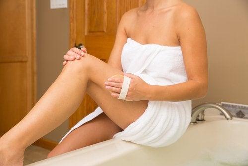Donna su vasca da bagno con asciugamano e spazzola per le gambe