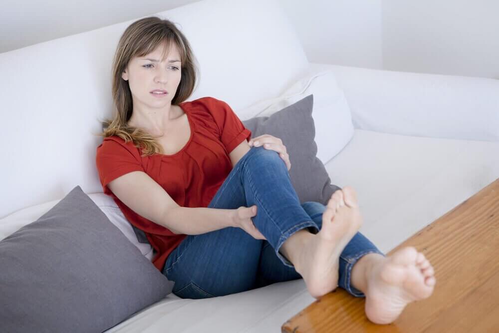 Donna sul divano con gambe doloranti