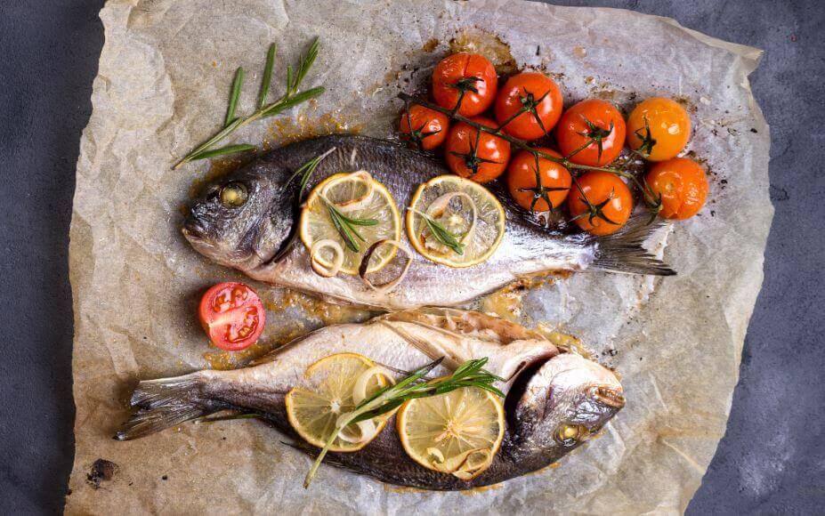 Pesce e verdure su carta da forno