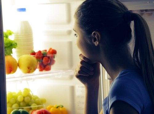 Ragazza davanti al frigorifero sceglie cosa mangiare