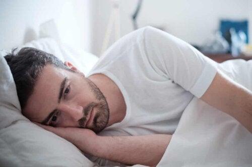 Uomo a letto che non dorme.