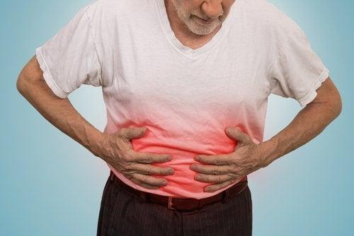Uomo con maglietta bianca colorata di rosso alla pancia a simboleggiare ulcera
