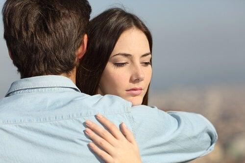Donna pensierosa abbraccia uomo