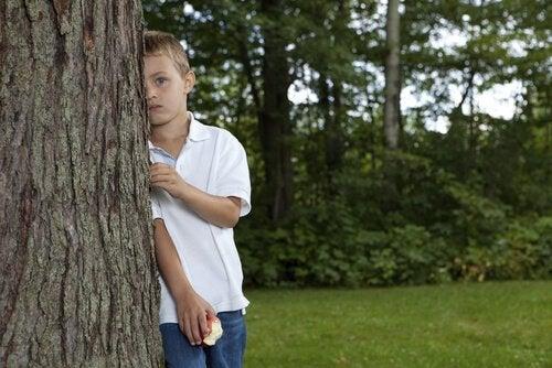 Bambino appoggiato a un albero