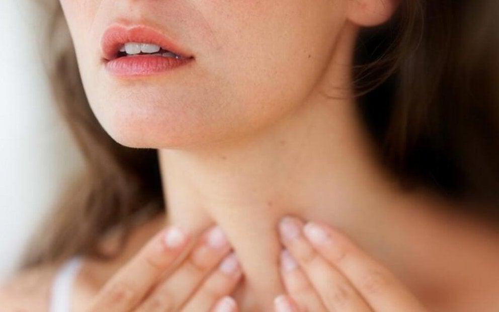 Donna che si tocca la tiroide