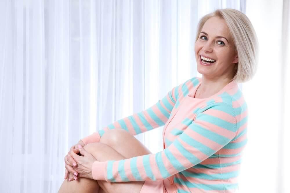 Donna in menopausa con vestito a righe sorridente