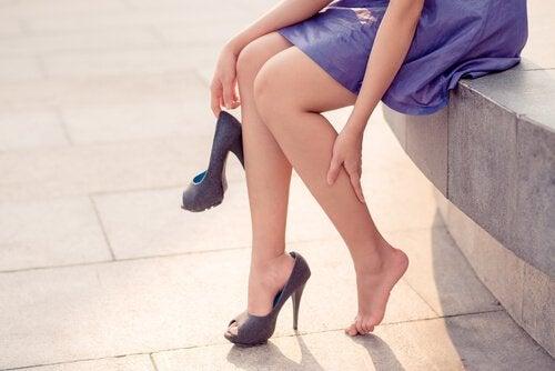 Donna con tacchi alti massaggia le gambe stanche