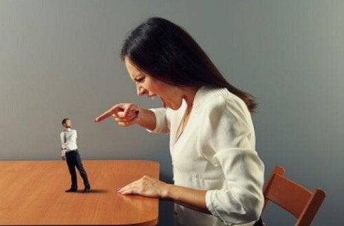 Donna punta il dito su un uomo in miniatura a rappresentare aggressione verbale