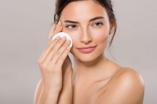Donna deterge il viso con un dischetto di cotone