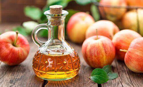 Bottiglia con aceto di mele e mele rosse