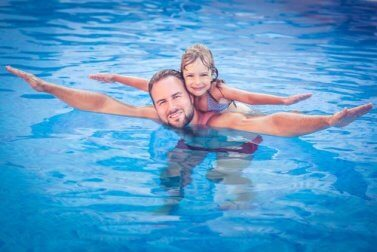 Bambina gioca con il papà in piscina