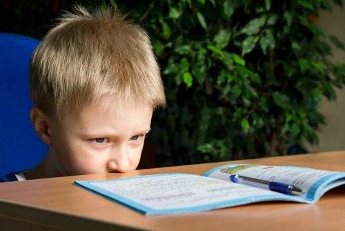 Bambino seduto davanti al quaderno aperto