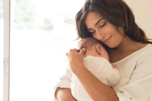 Donna abbraccia un neonato con tenerezza