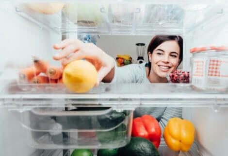 Trucchi mentali per perdere peso: donna che prende un limone dal frigorifero.