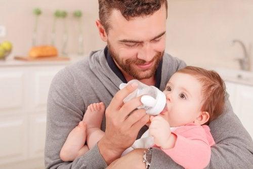 Padre nutre il neonato con il biberon