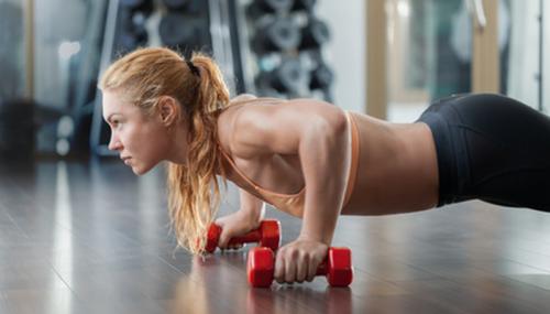 Ragazza bionda fa esercizi con i pesi