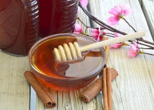 Contenitore di miele con rametti di cannella