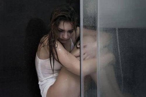 Ragazza triste piange rannicchiata sotto la doccia