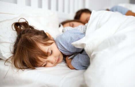 Bambina che dorme con i genitori.
