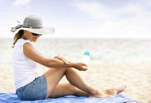 Donna che applica protezione solare per evitare le scottature solari
